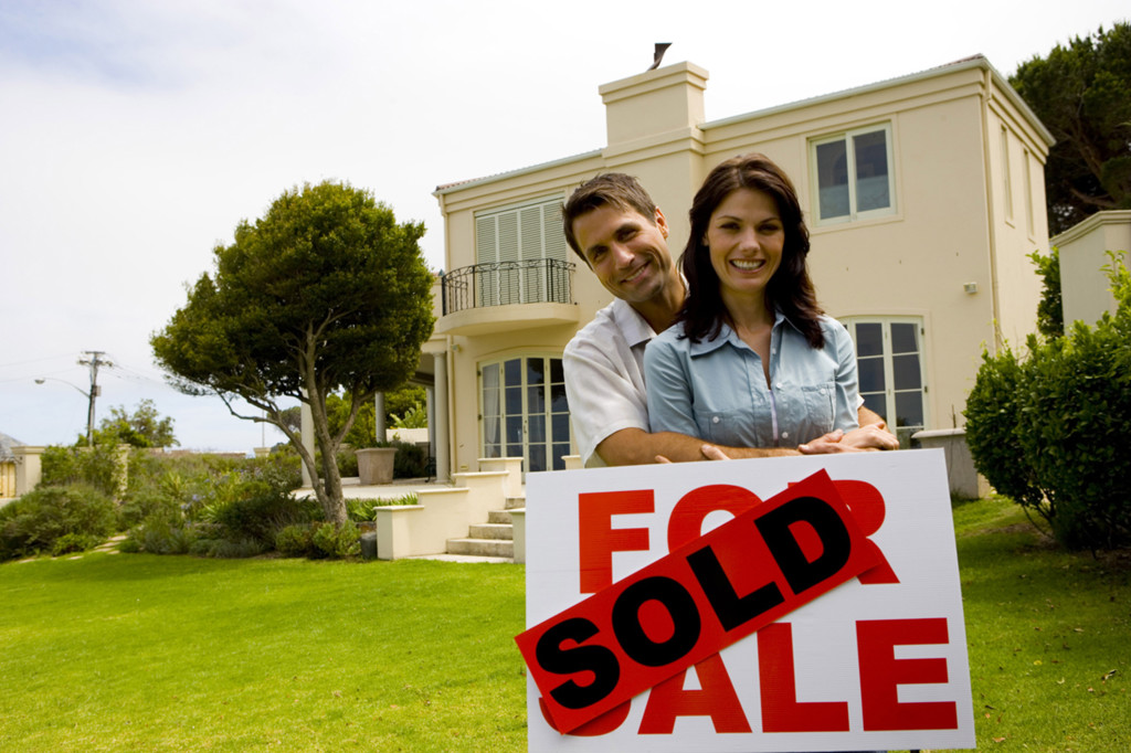 Couple with sold sign by house